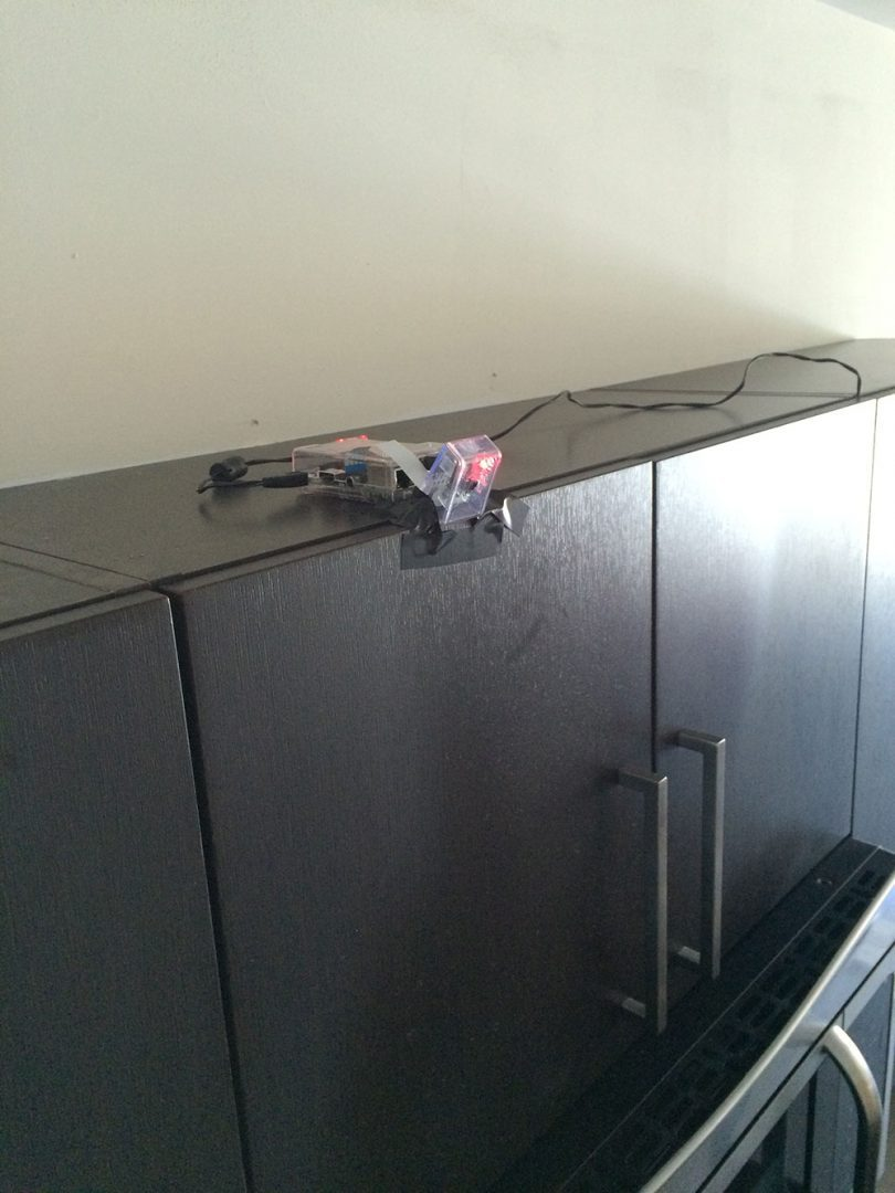 Figure 1: Mounting the Raspberry Pi to the top of my kitchen cabinets.